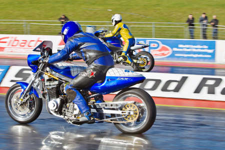 PODINGTON, UK - OCTOBER 6: An unnamed rider leaves the start line at the start of a quarter mile drag race at Santa Pod during the Extreme Performance Bike show on October 6, 2012 at Podington  Stock Photo - 16102290