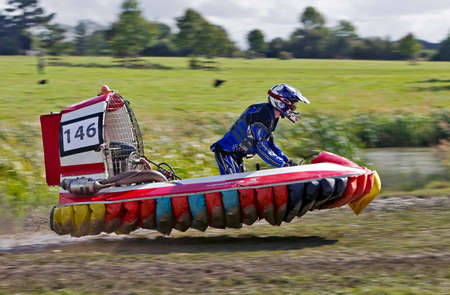 unnamed: CLAYDON, UK - SEPTEMBER 29: An unnamed driver in his F3 hovercraft takes flight between water and land during the HCGB UK National Championships final 2012 round on September 29, 2012 at Claydon Editorial