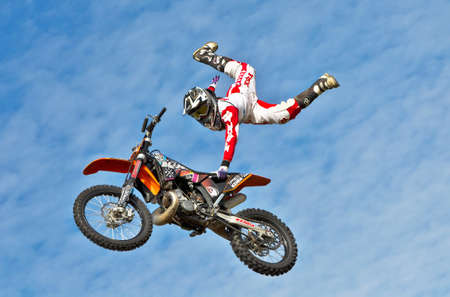 CULHAM, UK - SEPTEMBER 22: An unnamed stunt rider from the X-fighter team pulls a one handed air stunt for the watching public at the Red Bull Pro Nationals MX series on September 22, 2012 in Culham Editorial