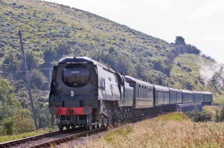 CORFE, UK - SEPTEMBER 8: Ex Southern Pacific loco, Manston, takes an early morning passenger train through Corfe just as the coastal mist begins to part over the hilltops on September 8, 2012 in Corfe  Stock Photo - 16860598