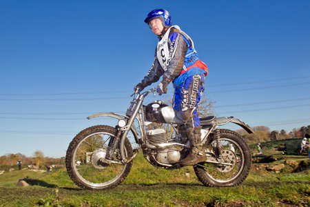 scrambler: BLEWBURY, UK - NOVEMBER 18: An unnamed rider exits an arena trial section on his vintage Greeves twinshock scrambler while participating in the NBMCC Downland Trial on November 18, 2012 in Blewbury  Editorial
