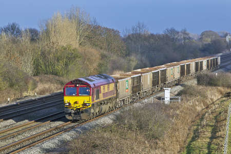 DENCHWORTH, UK - JANUARY 11: An EWS-MENDIP stone train approaches Denchworth on January 11, 2013 in Denchworth. Mendip Rail is an independant rail freight operator with a fleet of 454 dedicated wagons  Stock Photo - 18111940