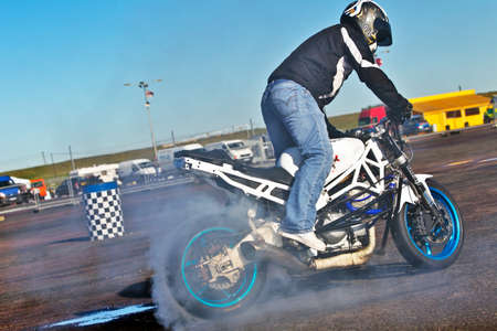 wheelspin: PODDINGTON, UK - OCTOBER 6: An unnamed stunt motorcycle rider gives a display of wheelies and doughtnuts to the public at the Santa Pod Straightliners meeting on October 6, 2012 in Poddington