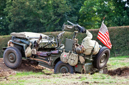 infantryman: HEADCORN, UK - AUGUST 11: The end of the battle re-enactment leaves an injured allied infantryman lying in the back of a Willys Jeep during the Combined Ops military show on August 11, 2012 in Headcorn  Editorial