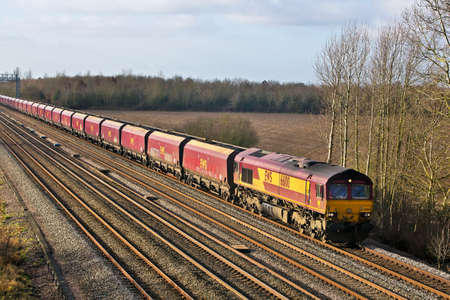 DENCHWORTH, UK - JANUARY 11: An EWS coal train bound for Didcot power station passes Denchworth On January 11, 2013 in Denchworth. EWS, part of DB Schenker is the UK is the UKs largest rail freight operator Stock Photo - 18111942