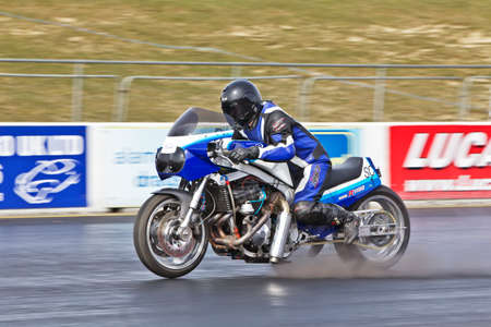 PODINGTON, UK - APRIL 7: An unnamed rider accelerates his Suzuki GSxR1100 motorcycle hard at the Santa Pod Raceway drag strip during the ACU Straight liners championship on April 7, 2013 in Podington Stock Photo - 19169326