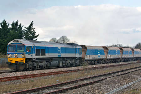 THEALE, UK - MARCH 13: An Aggregate Industries stone train leaves Theale on March 13, 2013 in Theale. Mendip Rail, an independant rail freight operator uses a fleet of 454 dedicated wagons  Stock Photo - 20511030
