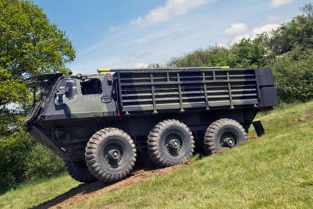 public demonstration: DENMEAD, UK - MAY 25: An Alvis Stalwart armoured personnel carrier exits a makeshift tank trap while giving a public demonstration at the Overlord show on May 25, 2013 in Denmead