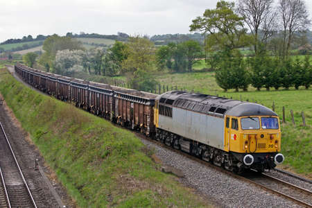 SAUNDERTON, UK - MAY 9:A 1976 built, class 56 diesel loco takes a freight train of spoil to Calvert plant on May 9, 2013 in Saunderton. The class56 was the first loco built in Rumania to be used by BR  Stock Photo - 20553384