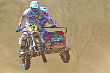 acu: ASHAM WOOD, UK - MAY 6: An unnamed pair of MX sidecar riders jump out of the dusty bombhole section at the Asham Wood round of the ACU UK national MX sidecar championships on May 6, 2013 in Asham Wood Editorial