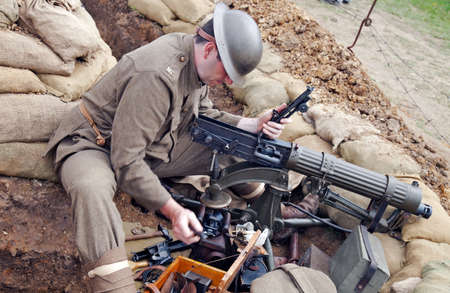 BELTRING, UK - JULY 19  A reenactor from a British WW1 group cleans his Vickers machine gun in a slit trench during the War   Peace show on July 19, 2019 in Beltring