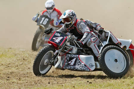 unnamed: PUTTENHAM, UK - AUGUST 14  An unnamed sidecar grasstrack team power around a bend at the H SMCC grasstrack championships on August 14, 2013 in Puttenham Editorial