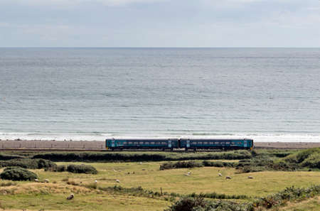 power operated: CRICCIETH, UK - AUGUST 12  An Arriva operated diesel train passes along the North Wales coast onroute to Portmadog on August 12, 2013 in Criccieth  Arriva operate on 243 stations using 131 power units Editorial