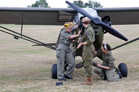 aircrew: HEADCORN, UK - AUGUST 17  Female ground crew reenactors repair the engine of a damaged Piper Cub at the Combined Ops military show on August 17, 2013 in Headcorn