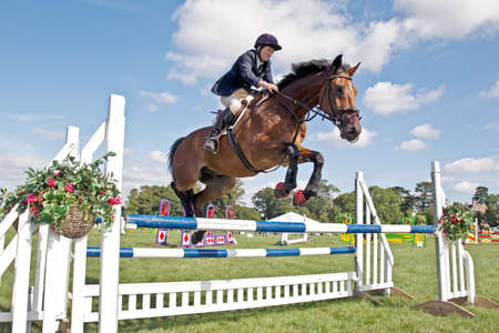 showground: WEEDON, UK - AUGUST 29  An unnamed rider negotiates a double poled fence in the horse show jumping championship at the Bucks County Show on August 29, 2013 in Weedon Editorial