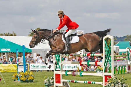 showground: WEEDON, UK - AUGUST 29  An unnamed rider competing in the expert show jumping competition at the Bucks County Show clears a particularly high jump gate on August 29, 2013 in Weedon