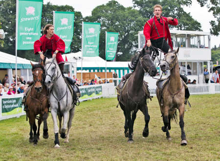 hants: BROCKENHURST, UK - JULY 31  Riders of the Devils Horsemen display race around the show ring standing on the back of two horses at the New Forest   Hants County Show on July 31, 2013 in Brockenhurst