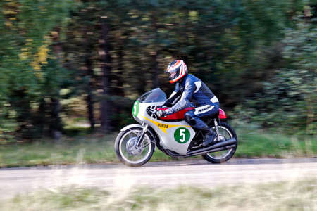 unnamed: EELMORE, UK - SEPTEMBER 29  An unnamed rider takes his vintage Honda motorcycle through the bends section of the VMCC Ossie Neal memorial Sprint race on September 29, 2013 in Eelmore