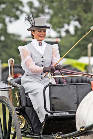 period costume: BROCKENHURST, UK - JULY 31  An unnamed female gig driver parades her horse   cart rig around the show ground at the New Forest Country Show dressed in period costume on July 31, 2013 in Brockenhurst  Editorial