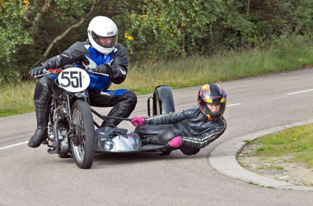 unnamed: EELMORE, UK - SEPTEMBER 29  An unnamed sidecar team take a tight left handed bend on their vintage motorcycle rig during the VMCC Ossie Neal memorial sprint on September 29, 2013 in Eelmore