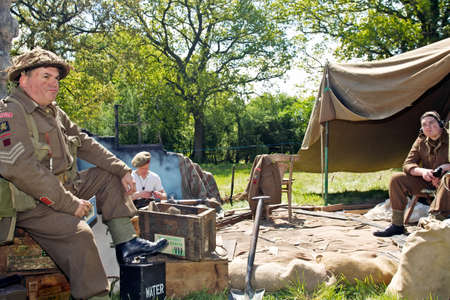 put forward: DENMEAD, UK - MAY 25  Members of the Wiltshire Regiment re-enactment group put on a realistic WW2 forward base camp display at the Overlord Military show on May 25, 2013 in Denmead Editorial