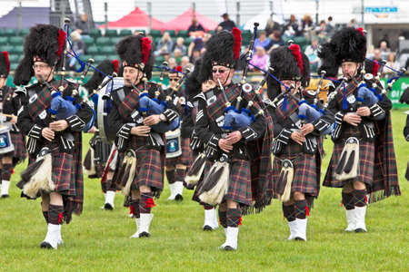 showground: NEWBURY, UK - SEPTEMBER 21  Scottish bagpipers play the popular tune  Flower of Scotland  to the watching public in the main arena at the Berks County Show on September 21, 2013 in Newbury