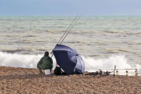 bloodsport: A lone sea fisherman on a pebbly beach fishing during a rising storm Stock Photo