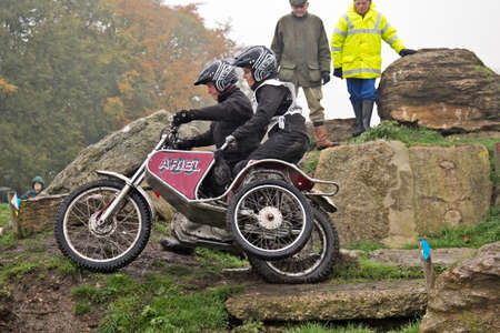 BLEWBURY, UK - NOVEMBER 17  An unnamed couple take their sidecar and motorcycle rig through a rocky section of Seymours Arena during the Downland Trophy challenge on November 17, 2013 in Blewbury