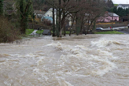 sustained: CENARTH, UK - DECEMBER 30  Flood waters threaten the surrounding roads and housing as the Afon Teifi river bursts its banks during a sustained period of heavy rainfall on December 30,2013 in Cenarth