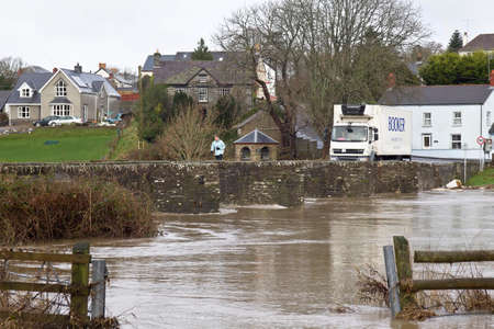 sustained: LLECHRYD, UK - DECEMBER 30  Flood waters threaten the surrounding roads and housing as the Afon Teifi river bursts its banks during a sustained period of heavy rainfall on December 30,2013 in Llechryd  Editorial