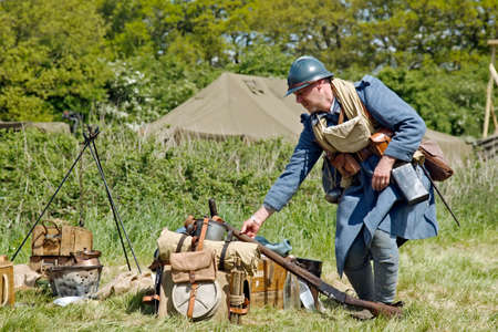 DENMEAD, UK - MAY 25  A reenactor dressed in French army serge from the WW1 era breaks camp on route to the trench area at the Overlord show on May 25, 2013 in Denmead
