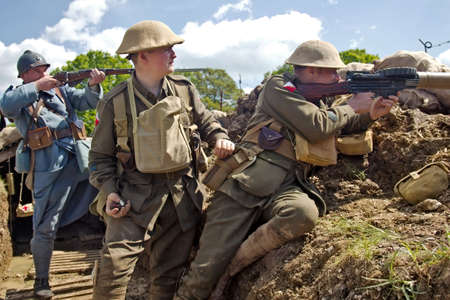 DENMEAD, UK - MAY 25  Reenactors dressed in French   Australian army uniform from the WW1 era fire from the edge of a trench in a snipers position at the Overlord show on May 25, 2013 in Denmead