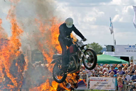 showground: WEEDON, UK - AUGUST 29  A rider of the Royal Signals White Helmets display team leaps through a fire ring in the main public arena at the Bucks County show on August 29, 2013 in Weedon