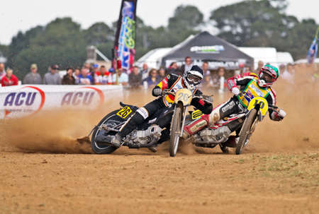 unnamed: SWINGFIELD, UK - AUGUST 18  An unnamed German international grasstrack rider  left  leads his Australian counterpart during the Longtrack grass world championships on August 18, 2013 in Swingfield