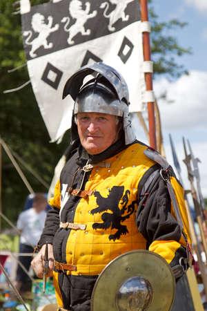 reenactor: POTTEN FIN, Reino Unido - 27 de julio: Un hombre medieval en reenactor brazos se prepara para luchar con la espada y el escudo en la feria de vapor Dacorum el 27 de julio de 2014 en Potten End Editorial