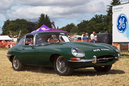 e 27: POTTEN END, UK - JULY 27: A classic E-type Jaguar sportscar leaves the main display arena having just completed its show to the public at the Dacorum Steam fair on July 27, 2014 in Potten End