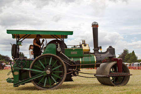 steam roller: POTTEN END, UK - JULY 27:  A large vintage road roller gives rides around the main display arena to members of the public at the Dacorum Steam fair on July 27, 2014 in Potten End Editorial
