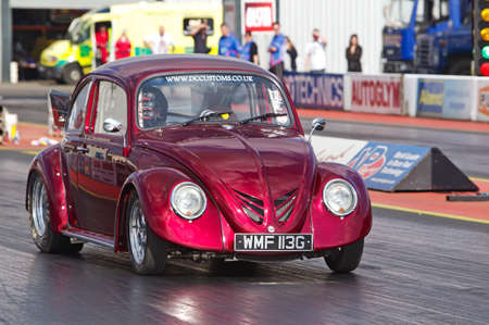 dragster: PODINGTON, UK - APRIL 11: An unnamed driver takes his dragster modified Beetle motorcar down the Santa Pod raceway at the Big Bang festival on April 11, 2014 in Podington