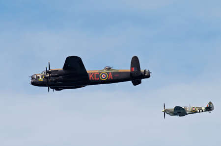 ASNELLES, FRANCE - JUNE 6: The Lancaster and Spitfire of the BBMF pass over Asnelles beach as part of the Normandy coast flypast during the D-Day 70th year celebrations on June 7, 2014 in Asnelles
