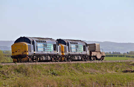 public safety: TEWKESBURY, UK - APRIL 16: A freight train carrying spent power station fuel heads to the recycling plant on April 16, 2014 in Tewkesbury. Freight of this type is hauled by two locos for public safety