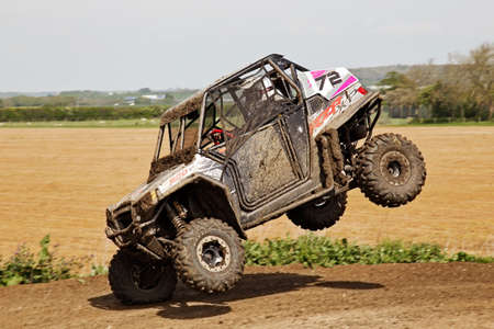 4 wheel: ARNCOTT, UK - MAY 4: An unnamed driver competing in the UK SXS RZR series lands awkwardly on the front offside wheel having just jumped the table-top on May 4, 2014 in Arncott