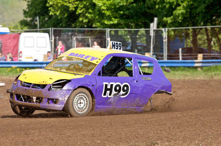 unnamed: STROUD, UK - MAY 3: An unnamed driver competing in the 2014 UKAC autograss series continues to race having lost a wheel on the top corner of the circuit on May 3, 2014 in Stroud