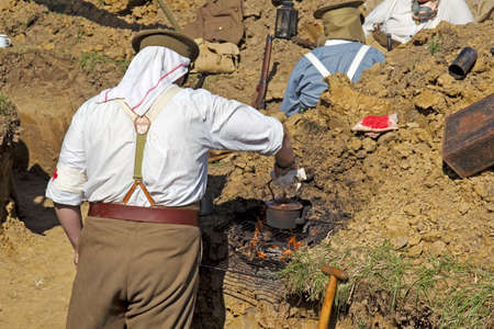 ww1: WESTERNHANGER, UK - JULY 16: Members of a WW1 British army re-enactment group brew up tea in their trench system at the War & Peace show on July 16, 2014 in Westernhanger Editorial