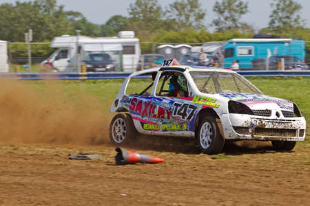 demarcation: STROUD, UK - MAY 3: An unnamed driver competing in Rd1 of the 2014 UKAC autograss series takes the top corner of the circuit close to the demarcation cones on May 3, 2014 in Stroud