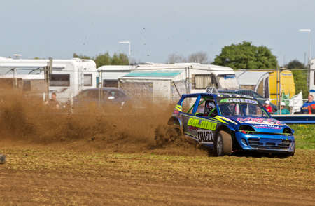 motorcar: STROUD, UK - MAY 3: An unnamed driver competing in Rd1 of the 2014 UKAC autograss series makes a long slide toward the boundary wire at the bottom corner of the race circuit on May 3, 2014 in Stroud