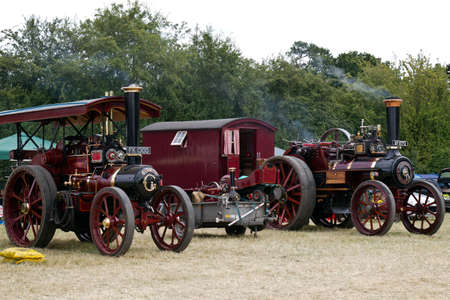 traction: POTTEN END, UK - JULY 27: A pair of vintage traction engines stand outside the main arena waiting to be ushered into the grand parade at the Dacorum Steam & Country fair on July 27, 2014 in Potten End