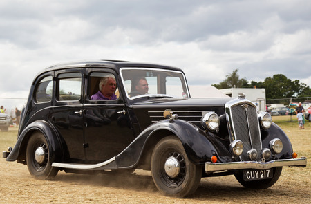 motorcar: POTTEN END, UK - JULY 27: A 1938 1460 Wolseley saloon heads toward the main display area at the Dacorum Steam fair on July 27, 2014 in Potten End Editorial