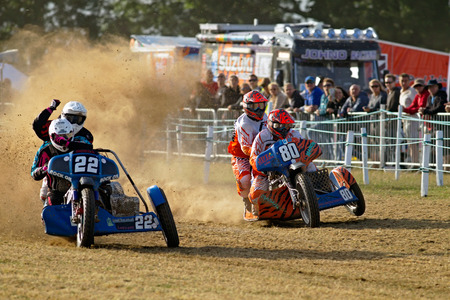 sidecar: SWINGFIELD, UK - AUGUST 18: Competitors racing in the UK sidecar Nat Champs approach the finish line during one of the heat races at the FIM World Grasstrack Champs on August 18, 2013 in Swingfield
