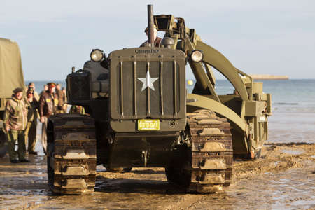 ww2: AROMANCHES, FRANCE - JUNE 6: A WW2 vintage bulldozer prepares the ground for the heavy armoured vehicles to safely get onto the beach during the D-Day celebrations on June 6, 2014 in Aromanches