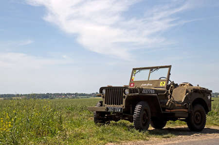 allied: AROMANCHES, FRANCE - JUNE 6: A vintage WW2 Jeep is parked outside an allied soldiers war cemetery before attending the 70th D-Day anniversary celebrations on June 6, 2014 in Aromanches